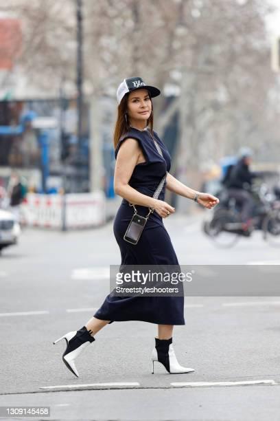 Model and DJane Gitta Saxx wearing a dark blue top by Sonja Kiefer Studio, a dark blue wrap skirt by Sonja Kiefer Studio, a dark blue and white cap...
