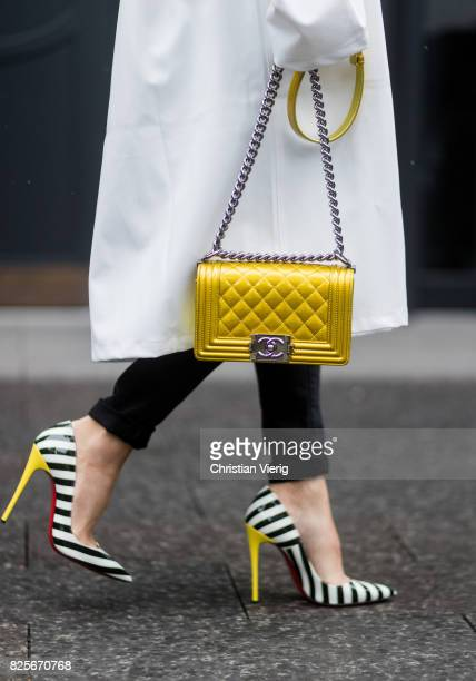 Model and fashion blogger Alexandra Lapp Chanel handbag detail wearing a white oversized raincoat with a hood from Vetements yellow golden lacquer...