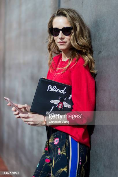 Model and fashion blogger Alexandra Lapp wearing a black and multicoloured floral print trousers from Fendi featuring a high rise a concealed front...