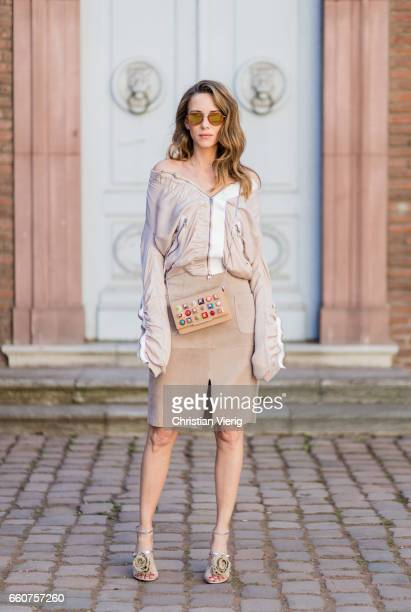Model and fashion blogger Alexandra Lapp wearing a bomber jacket by Tigha which has a slightly shimmering fabric with feminine ruffled parts and...
