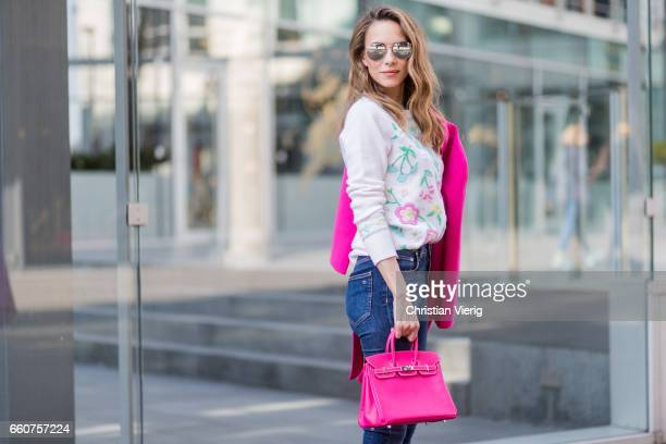 Model and fashion blogger Alexandra Lapp wearing a cashmere pullover from Heartbreaker with precious details of sewed on colorful pastel flowers slim...