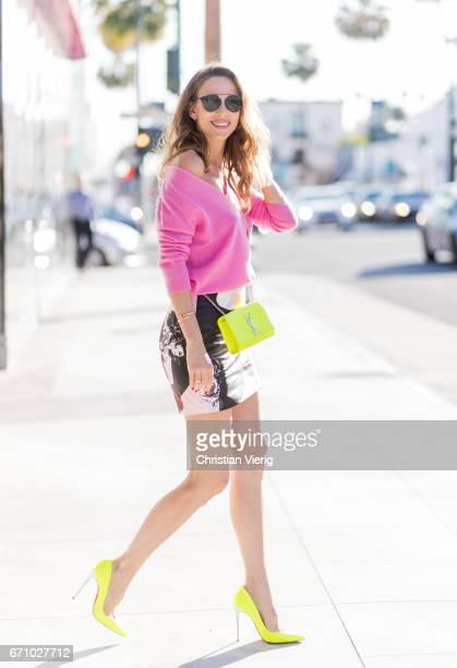 Model and fashion blogger Alexandra Lapp wearing a multicolor mini leather skirt by Prabal Gurung pink V neck cashmere pullover from Heartbreaker...