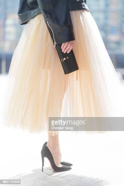 Model and fashion blogger Alexandra Lapp wearing a multicolored sleeveless brocade tulle dress from Natasha Zinko a black biker leather jacket with...