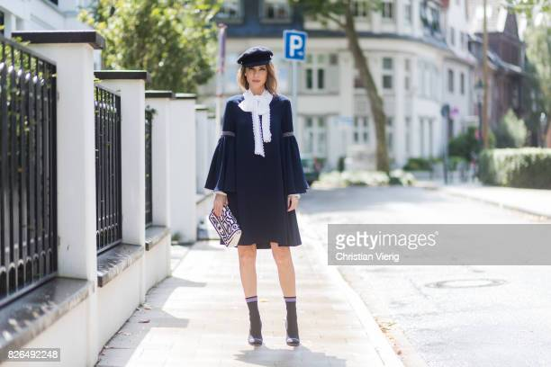 Model and fashion blogger Alexandra Lapp wearing a navy dress with oversized sleeves and a white tieneck blouse from Steffen Schraut Chanel tweed cap...