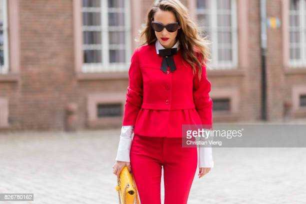 Model and fashion blogger Alexandra Lapp wearing a red slim fit suit from Steffen Schraut, blazer with peplum and red pants, white blouse with a...