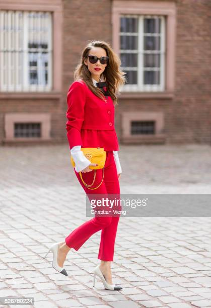 Model and fashion blogger Alexandra Lapp wearing a red slim fit suit from Steffen Schraut blazer with peplum and red pants white blouse with a black...