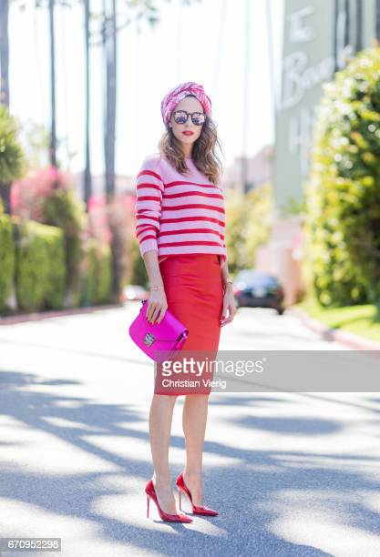 Model and fashion blogger Alexandra Lapp wearing a red stretch leather pencil skirt from American Retro pink and red striped cashmere pullover by...