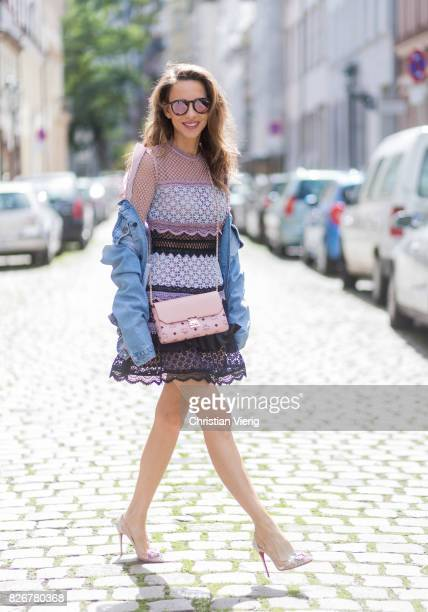 Model and fashion blogger Alexandra Lapp wearing a SelfPortrait dress out of lace oversized denim jacket from SET Christian Louboutin Feerica heels...