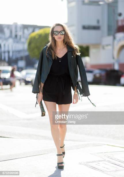 Model and fashion blogger Alexandra Lapp wearing a short playsuit wich combines a semitransparent top part with kimono sleeves without shoulder seams...