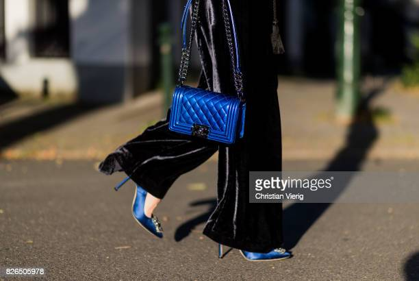 Model and fashion blogger Alexandra Lapp wearing a V neck velvet jumpsuit from Vivetta with a cord belt, blue metallic lacquer Boy bag by Chanel,...