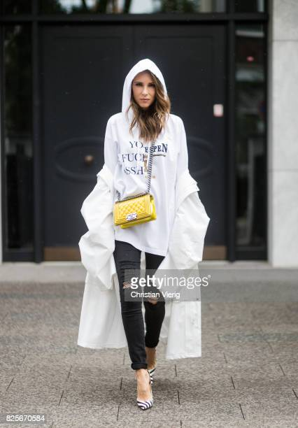 Model and fashion blogger Alexandra Lapp wearing a white oversized raincoat with a hood from Vetements Vetements hoodie in white printed with a part...