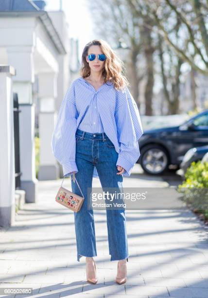 Model and fashion blogger Alexandra Lapp wearing an oversized navy and white striped cotton shirt, cut for an oversized fit with a point collar and...