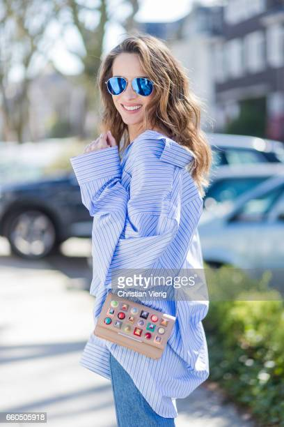 Model and fashion blogger Alexandra Lapp wearing an oversized navy and white striped cotton shirt cut for an oversized fit with a point collar and...