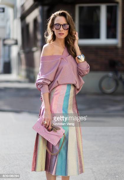 Model and fashion blogger Alexandra Lapp wearing metallic chic pleated lame skirt in shimmering pastel pink metallic vneck knit by Alberta Ferretti...
