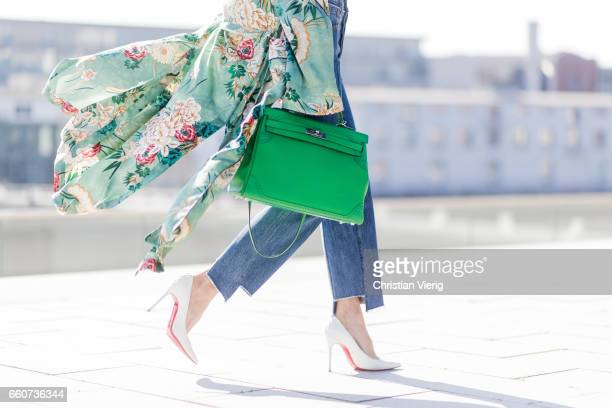 Model and fashion blogger Alexandra Lapp wearing wearing a green flower printed kimono from Zara a green tank top in silk blue jeans from Vetements...