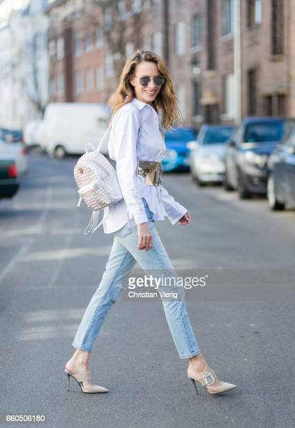 Model and fashion blogger Alexandra Lapp wearing wearing a white shirt from Steffen Schraut Levis 501 skinny jeans brown mules with a shiny buckle...