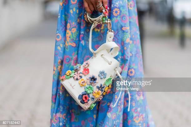 Model and fashion blogger Gitta Banko wearing a floral-patterned dress and a pastel-green oversize waist belt by Marina Hoermanseder, a Kasper...