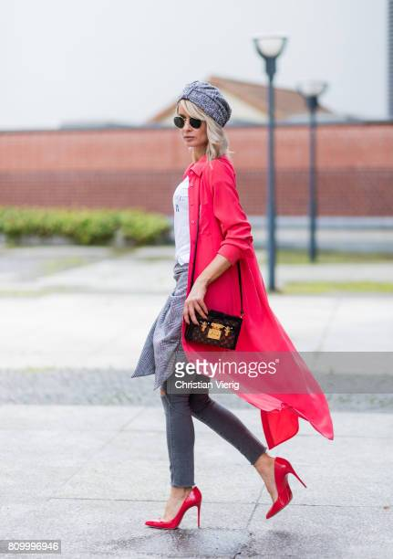 Model and fashion blogger Gitta Banko wearing a hibiscus-colored stretchy silk dress as a coat by Jadicted, light-grey jeans in destroyed look from...