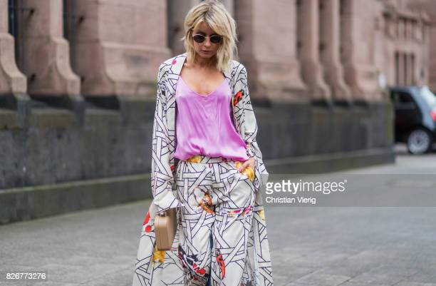 Model and fashion blogger Gitta Banko wearing a kimono and silk trousers in Bauhauskoi carp print pattern by Dawid Tomaszewski a pink silk top from...