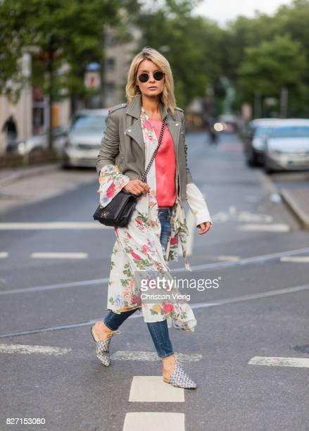 Model and fashion blogger Gitta Banko wearing a light grey biker leather jacket by Iro a pink top by Marina Hoermanseder floralpatterned silk dress...
