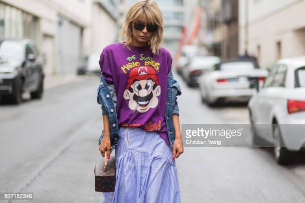 Model and fashion blogger Gitta Banko wearing a stripped pleatedskirt with a cut by Main Label purple handpainted tshirt with Super Mario Bros design...