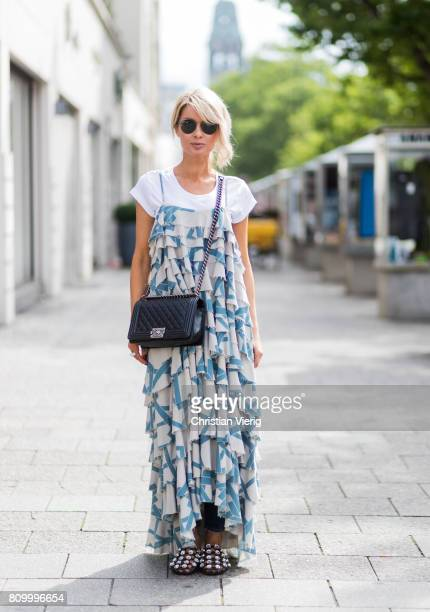 Model and fashion blogger Gitta Banko wearing a white organic-cotton statement t-shirt from the LOOKABE x BLONDWALK collection underneath a silk with...