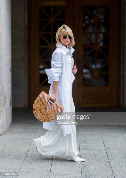 Model and fashion blogger Gitta Banko wearing a white silk top by Jadicted, white oversized blouse by Balossa, a figure-hugging white silk skirt by...