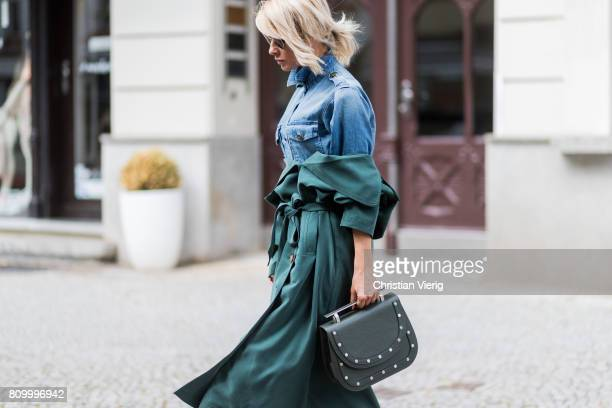 Model and fashion blogger Gitta Banko wearing an olivegreen cotton trench coat by MTWTFSS Weekday tally jeans blouse in military look by Current...
