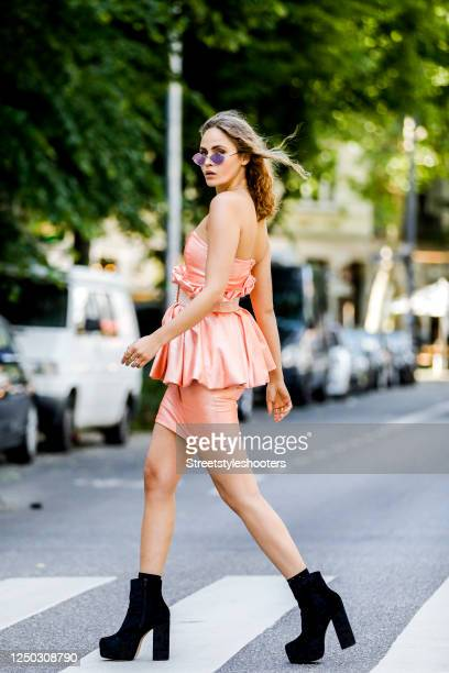 Model and influencer Elena Carriere wearing a apricot colored dress with peplum and a apricot colored belt by Marina Hoermanseder, black booties by...