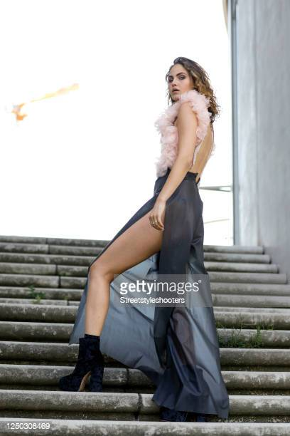 Model and influencer Elena Carriere wearing a rose colored bustier with black buckles and dark grey foil fabric pants with open sides by Marina...