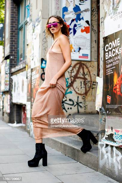 Model and influencer Elena Carriere wearing a salmon-colored delicate chain dress by Marina Hoermanseder, black booties by urban outfitters and...