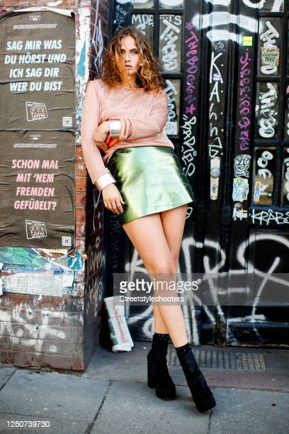 Model and influencer Elena Carriere wearing a salmon-colored sweater and a green skirt by Marina Hoermanseder, black booties by urban outfitters and...