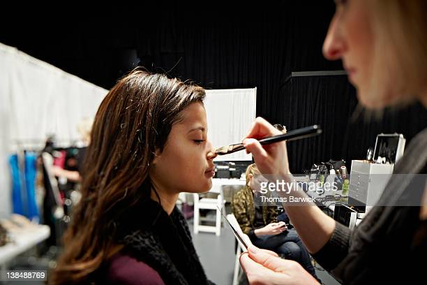 Model and make-up artist backstage at fashion show