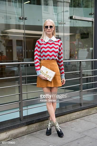 Model and Socialite Poppy Delevigne wears an Edie Parker clutch bag Miu Miu sweater Frame Denim skirt day 4 of London Womens Fashion Week...