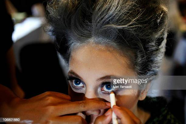 A model and stylist apply makeup in backstage area during the Dewi Fashion Knights show at Pacific Place on the sixth and final day of Jakarta...