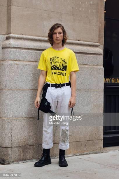 Model Andrew Hubert wears a yellow Paccbet/Rassvet shirt white pants Alyx belt and black boots uring New York Fashion Week Men's Spring/Summer 2019...