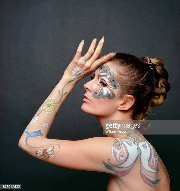 Model Angela Howard with body paint on her shoulder arm and face 1968 She has a butterfly on her shoulder flowers with a bee on her arm and a peacock...