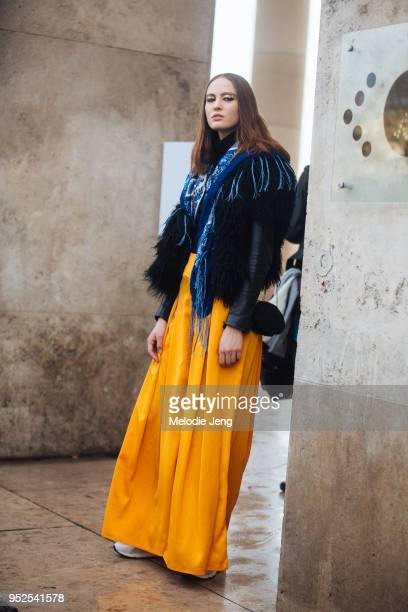 Model Ania Chiz wears the goldflake eye makeup from the Akris show a blue scarf over a black leather and shaggy fur jacket and gold/yellow widelegged...