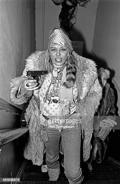 Model Anita Pallenberg holds handgun as she a climbs the stairs to the VIP room at the Mudd Club New York New York February 10 1980