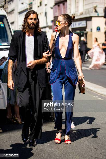 Model Anna Cleveland wearing a blue top with matching pants yellow sunglasses and silver and red heels is seen outside Jean Paul Gaultier show during...
