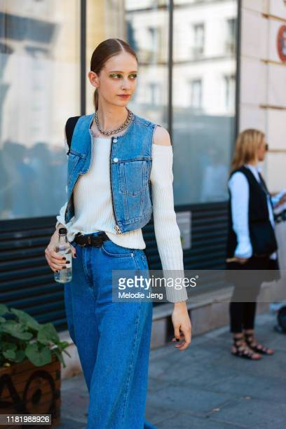 Model Anna Francesca wears a denim vest, white sweater, and blue jeans after the Jean Paul Gaultier show during Couture Fashion Week Fall/Winter 2019...