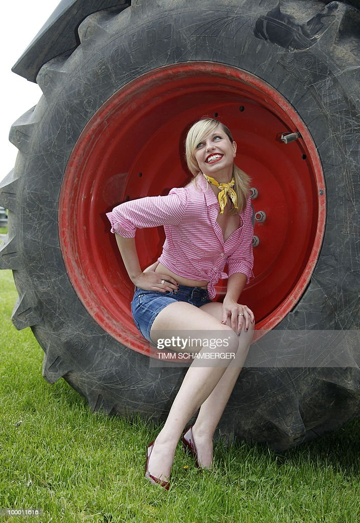 Model Anna Maria poses in the wheel of a tractor during a photocall to promote the 'Young Farmers Calendar 2011' on a farm in Schraudenbach, southern Germany, on May 20, 2010. More than 250 young women have applied to become one of the calendar's motives.