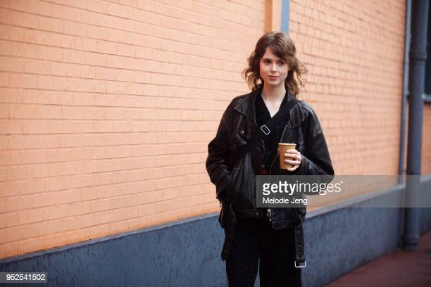 Model Anna Ulvklo holds a cup and wears a black leather jacket fanny pack and pants after the Balenciaga show on March 04 2018 in Paris France