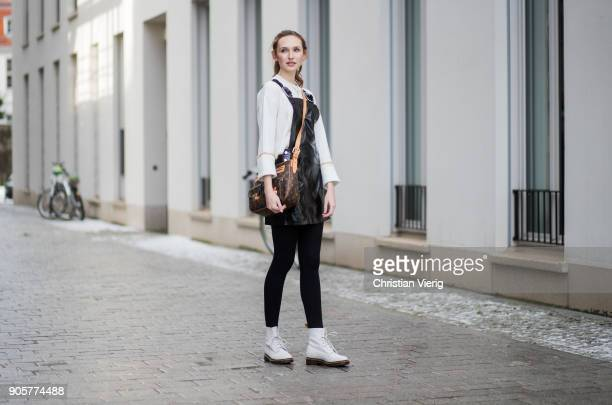 Model Anna Wilken wearing white Topshop knit black vinyl overall Mango Louis Vuitton bag white Dr Martens boots is seen during the Berlin Fashion...