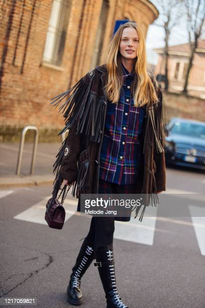Model Anne Vyalitsyna wears a brown fringe jacket blue plaid shirt maroon bag and black lace up boots after the Salvatore Ferragamo show during Milan...
