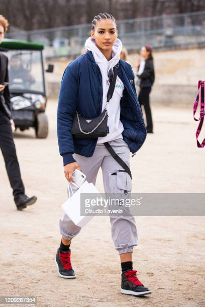Model Anyelina Rosa, wearing a white sweatshirt, grey pants, Nike sneakers, blue jacket and Prada bag, is seen outside Dior, during Paris Fashion...