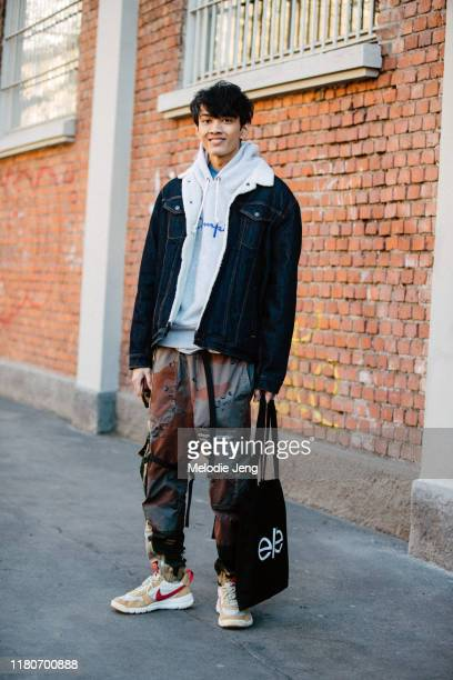 Model Arun Gupta wears a denim shearling-lined jacket, gray Champion hoodie, Off-White Men's Reconstructed Camo-Print Cargo Pants, and tan Nike...
