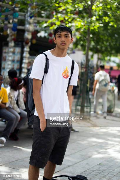 Model Arun Gupta wears a tshirt with a flame and black shorts during Paris Fashion Week Men's Spring/Summer 2018 on June 22 2017 in Paris France