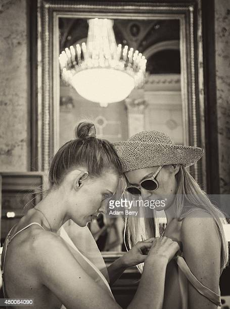 A model assists another as they prepare to go onto the runway backstage at the Malaikaraiss show during MercedesBenz Fashion Week Berlin...