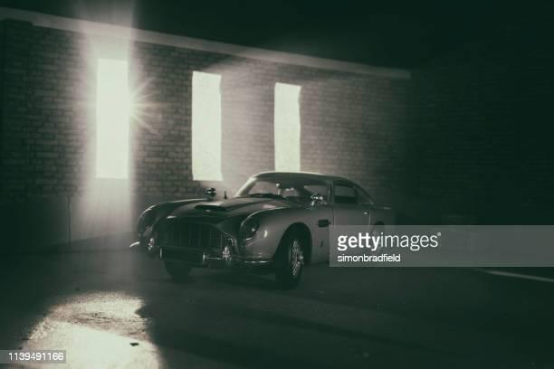 model aston martin db5 in atmospheric garage - james bond fictional character stock-fotos und bilder